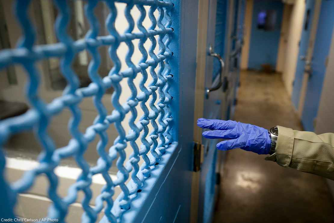 A gloved hand points to a holding cell in a Los Angeles jail.