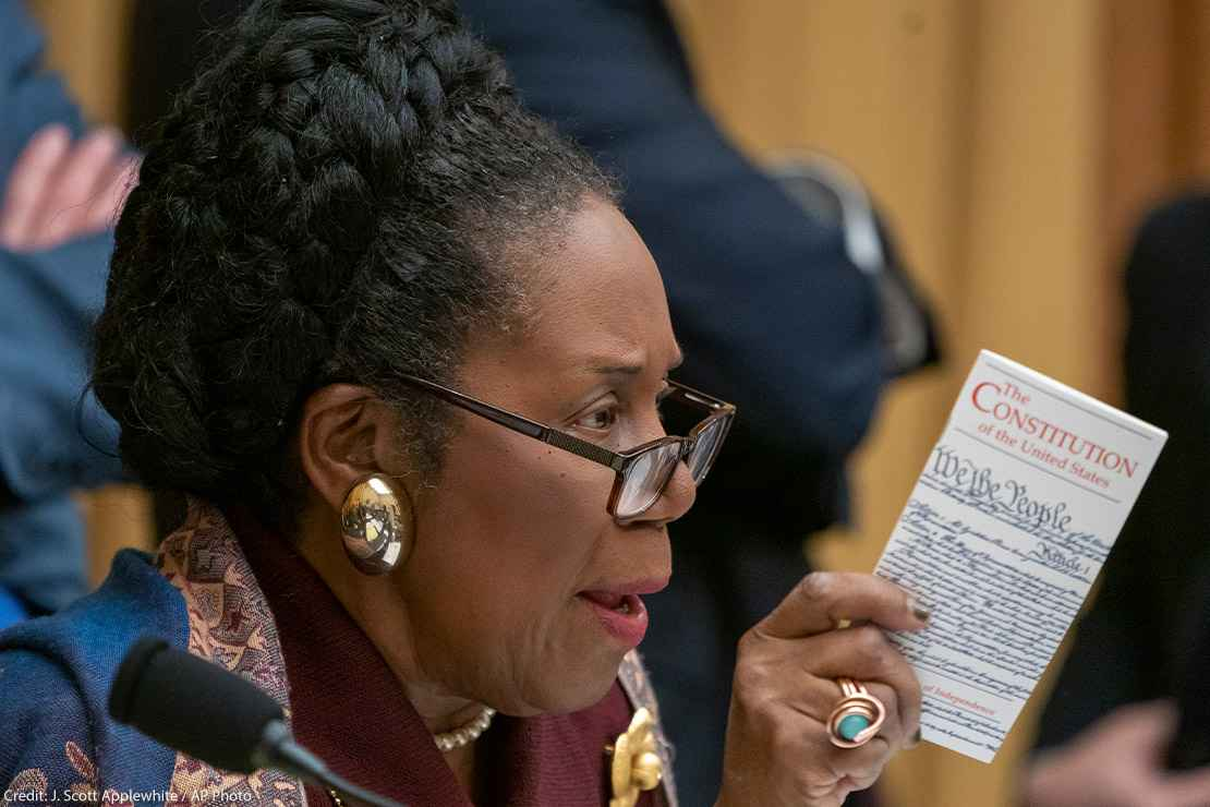 Rep. Sheila Jackson holds a pocket-size copy of The Constitution during a House committee hearing.