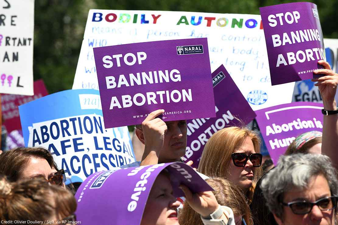 """Pro-abortion activists hold placards that read """"Stop Banning Abortion"""" during a rally at the Supreme Court"""