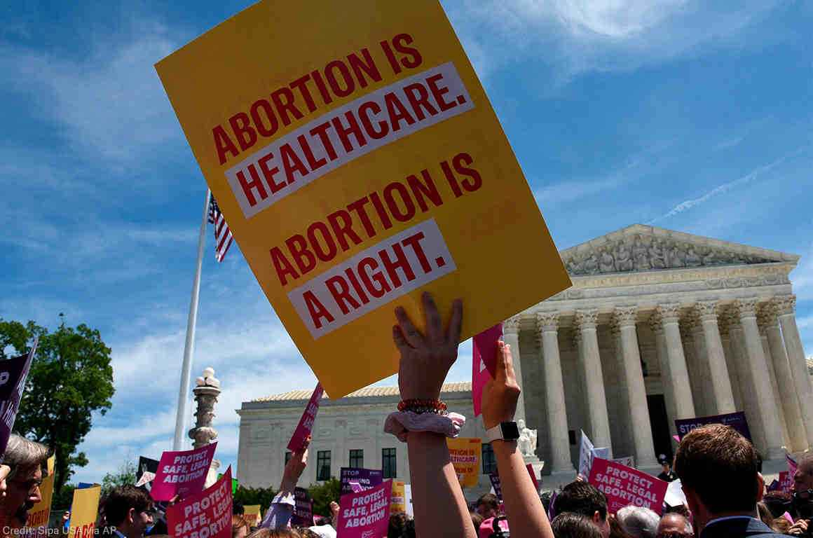 "Image: A photo shows the US Supreme Courthouse in the background. Angled upwards, the camera captures the heads and arms of a large crowd of people. Directly in focus is an arm raising a sign that says ""Abortion is healthcare. Abortion is a right."""