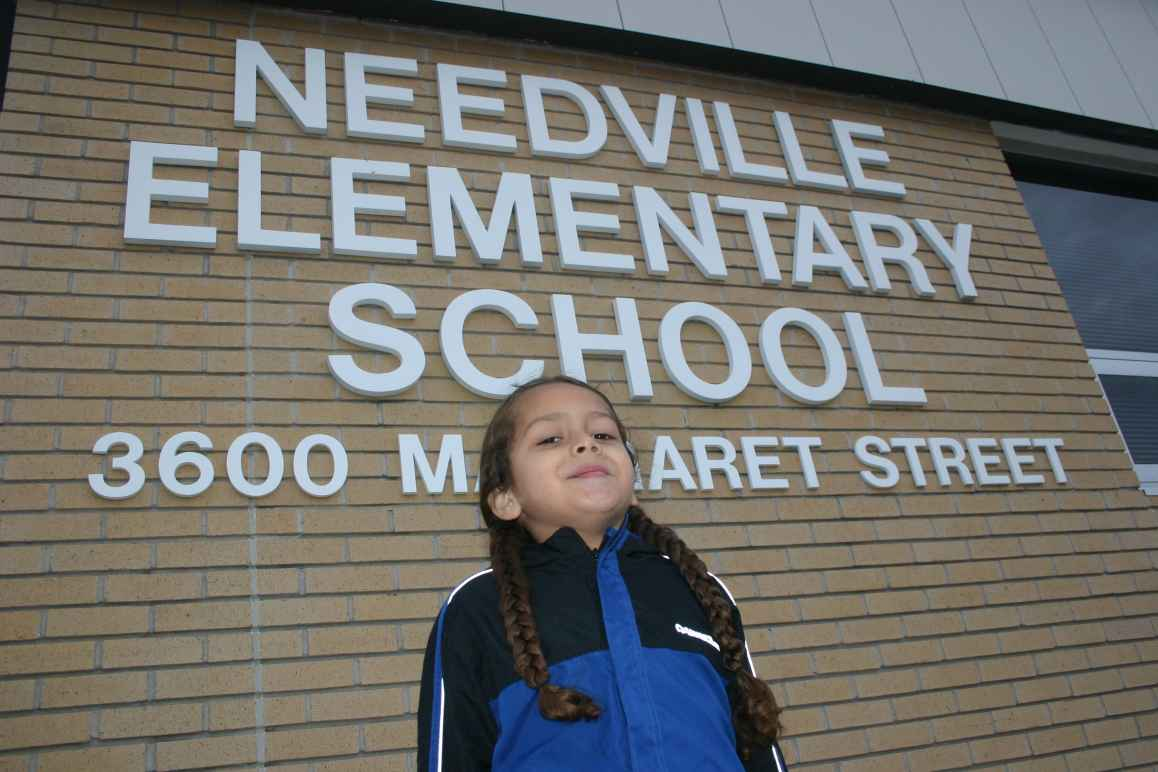 Image of Needville client in front of elementary school