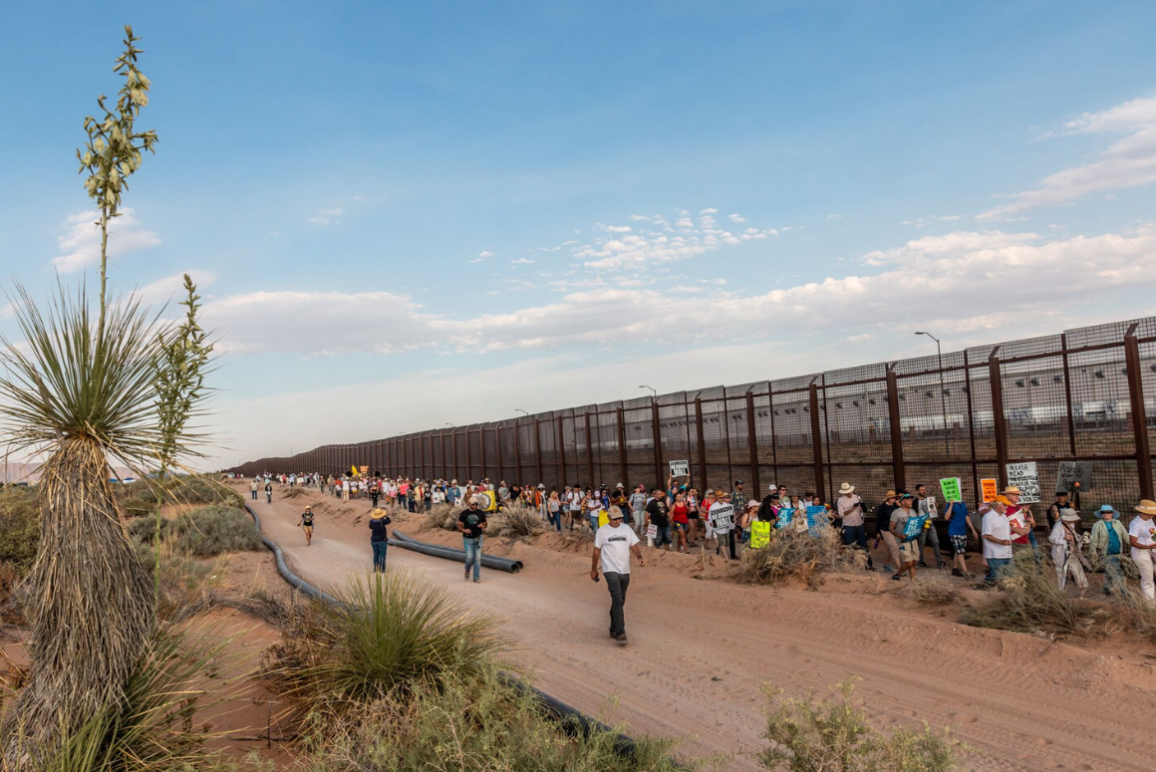 Immigrants' rights supporters lined up to march alongside a stretch of Border Wall in El Paso, Texas