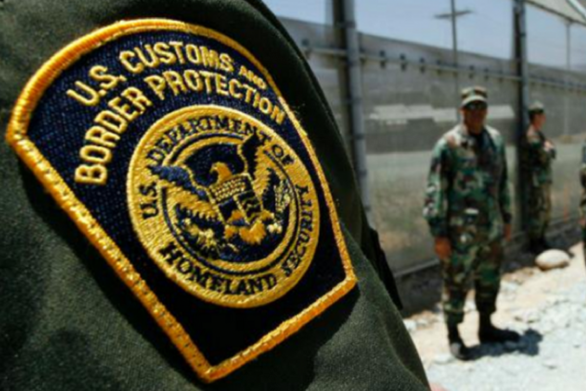 Photo: A Customs and Border Protection patch is worn on a green uniform. The CBP officer's arm takes us most of the photo, a fence and another CBP officer stand in the background.