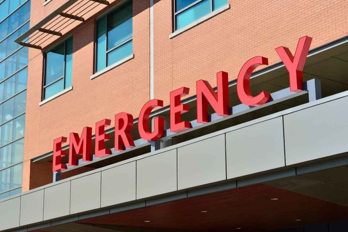"""Photo: A sign is displayed on a building with letters that spell """"Emergency."""""""