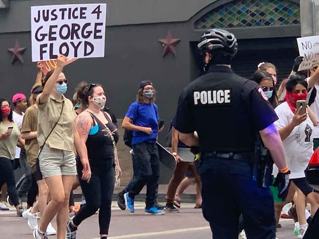 Photo: A police officer looks on as a crowd of people march past at a downtown Houston intersection. In focus is a person holding up a sign that says 'Justice 4 George Floyd.'