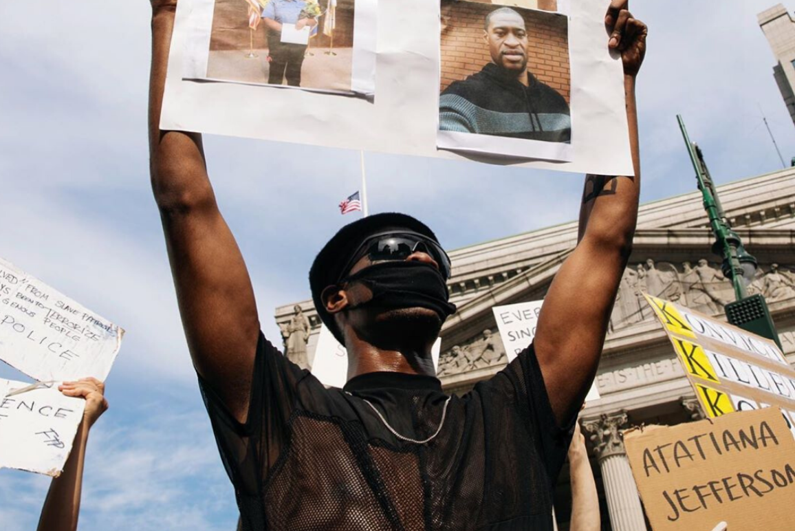 Photograph of black man protesting holding a George Floyd poster above his head