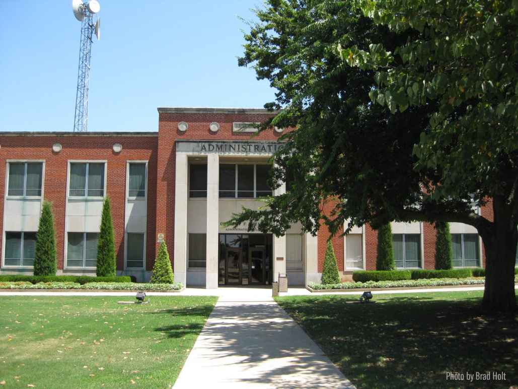 Photo: A tree in the foreground obscures a portion of a brick administration building in the background