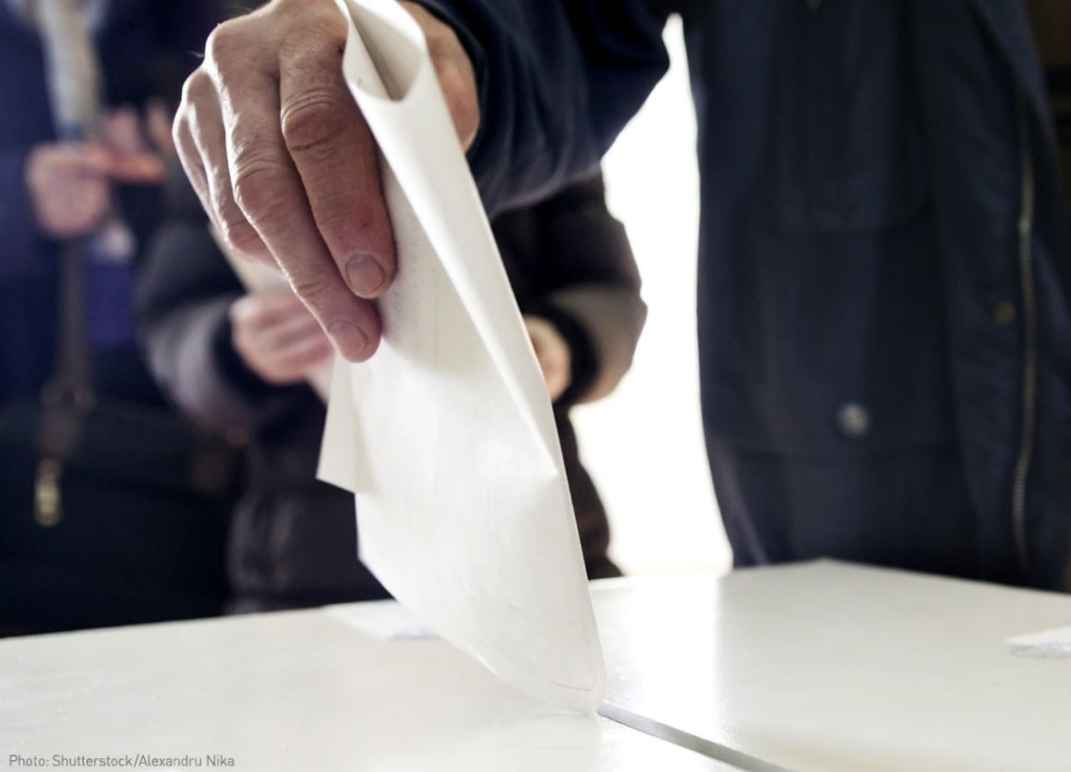Voter casting his vote in ballot box