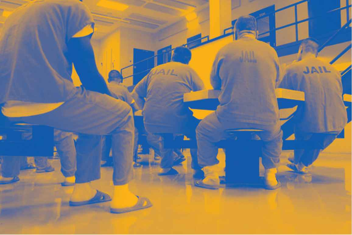 """Image: A stylized photo shows men wearing uniforms that say """"Jail"""" on their backs. They sit around tables in a carceral facility"""