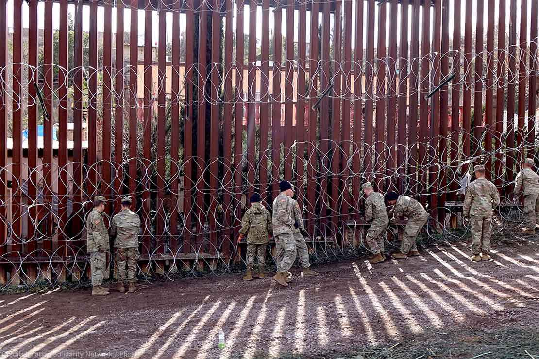 US military members are seen next to a red metal and barbed wire fence at the US border