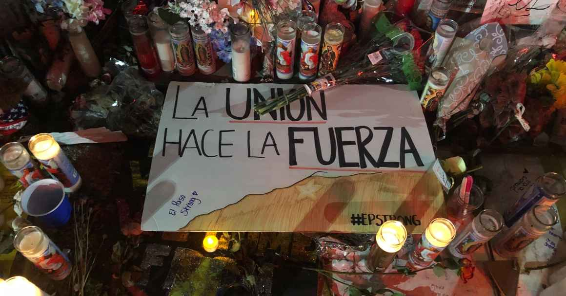 "Photo: Handwritten signs, candles, and flowers adorn a section of a street. Pictured at center is a sign that says ""La union hace la fuerza."""