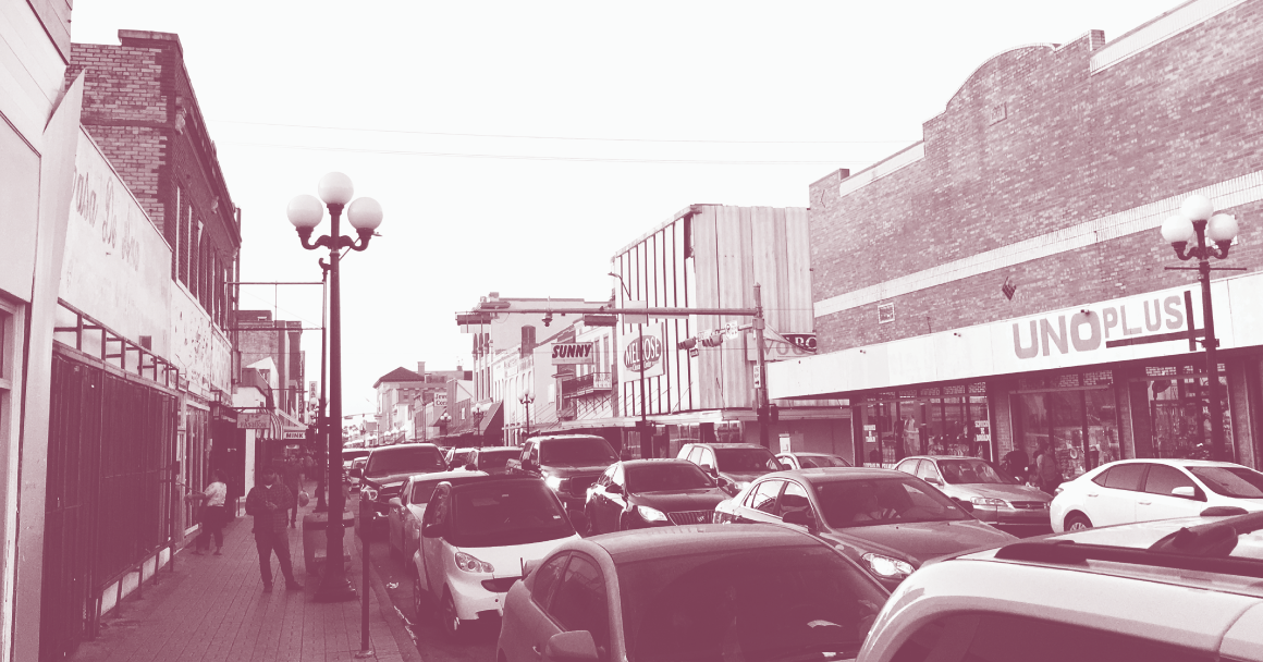 Image: A stylized photo of downtown Brownsville with cars parked one after the other on both sides of the street curb. Low-rise buildings stand on both sides.