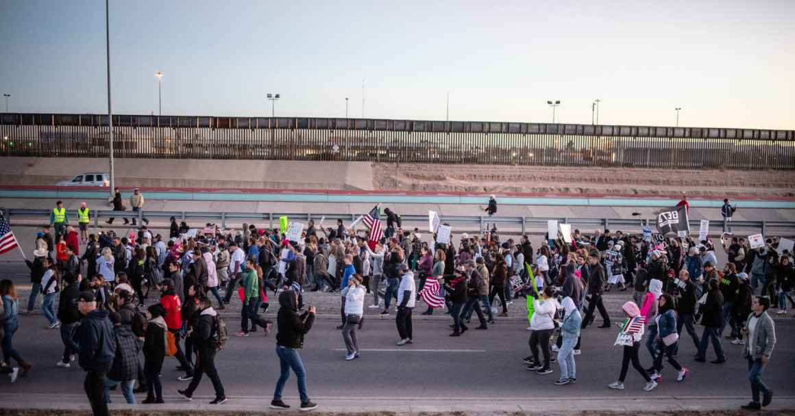 Photo: A large crowd streams by a a freeway and border fencing. They carry signs and american flags, walking in a general procession.