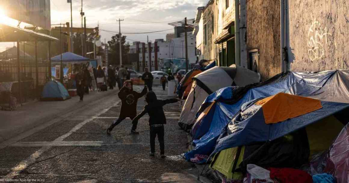 Image: A photo shows children playing next to tents pitched on a street in Mexico.