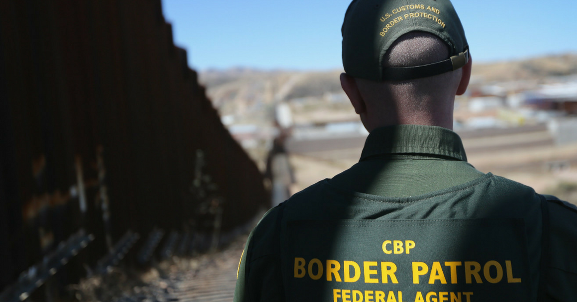 A photo shows a Border Patrol officer standing in the shadow of a border barrier. His back faces the camera and the barrier extends all the way to the horizon.