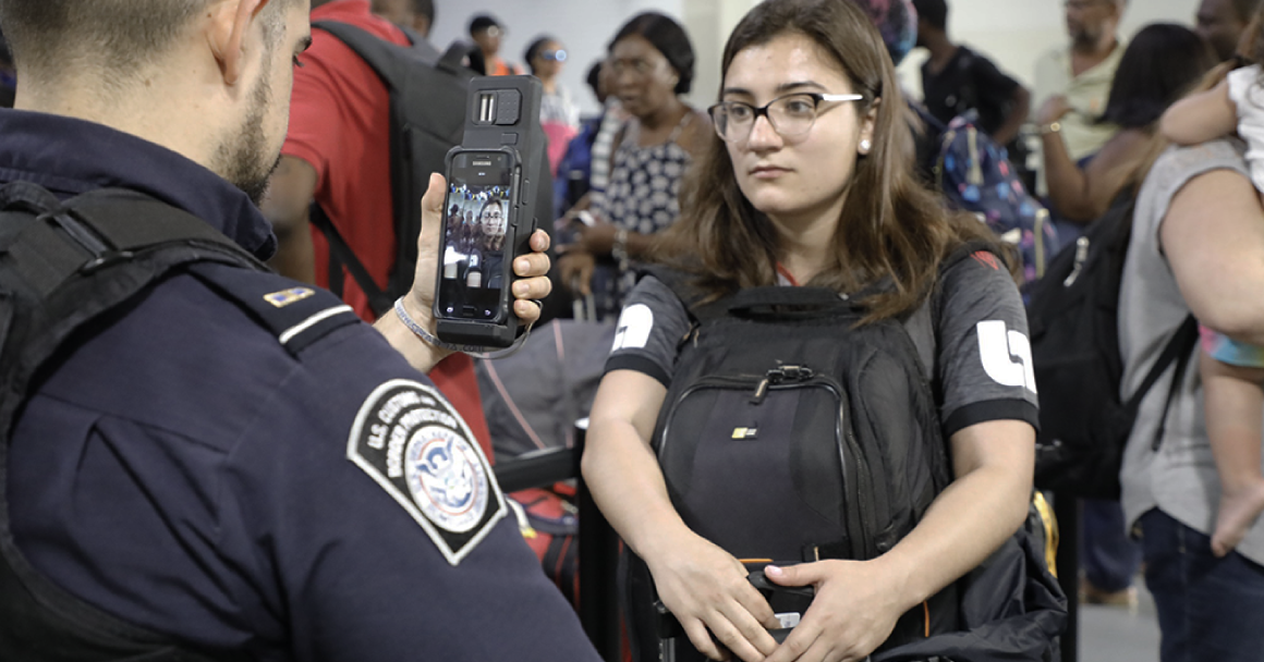 CBP agent scanning the face of a young woman using his smart phone