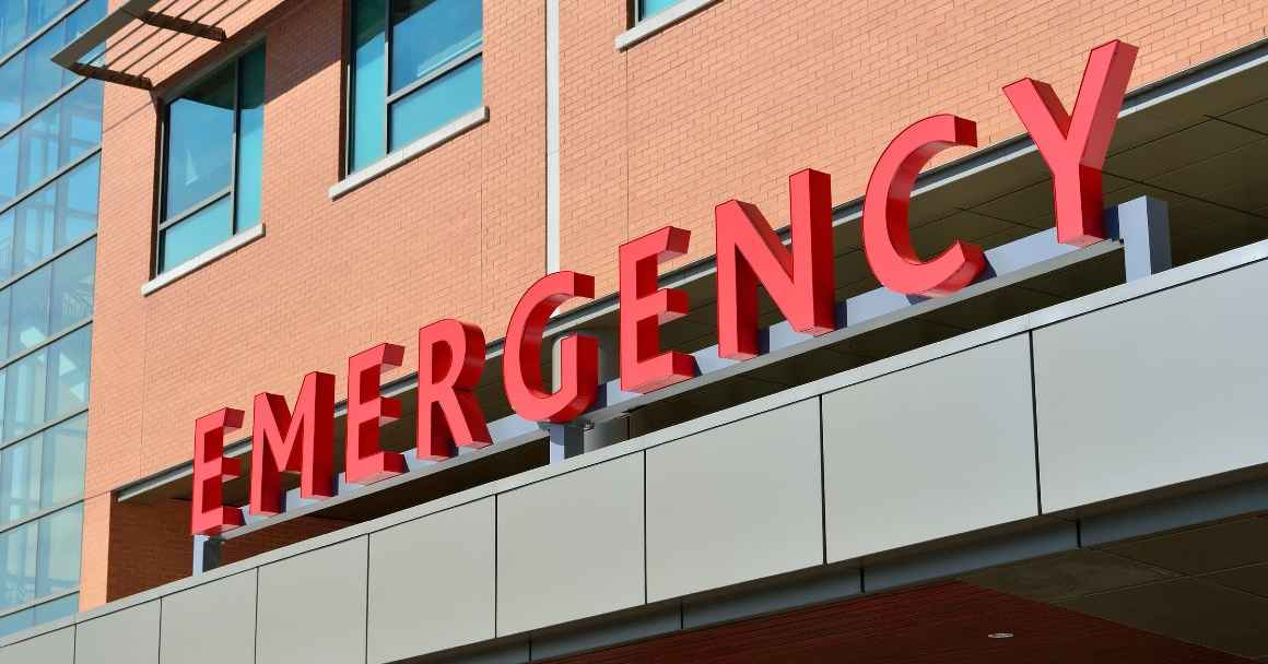 "Photo: A sign is displayed on a building with letters that spell ""Emergency."""