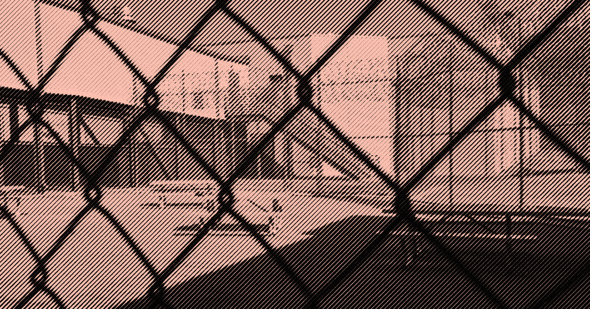 Image: A stylized photo shows an outdoor area of a detention center with some benches and tables. It is surrounded by barbed wire and concertina wire. The camera's view is partially obscured by the barbed wire fencing.